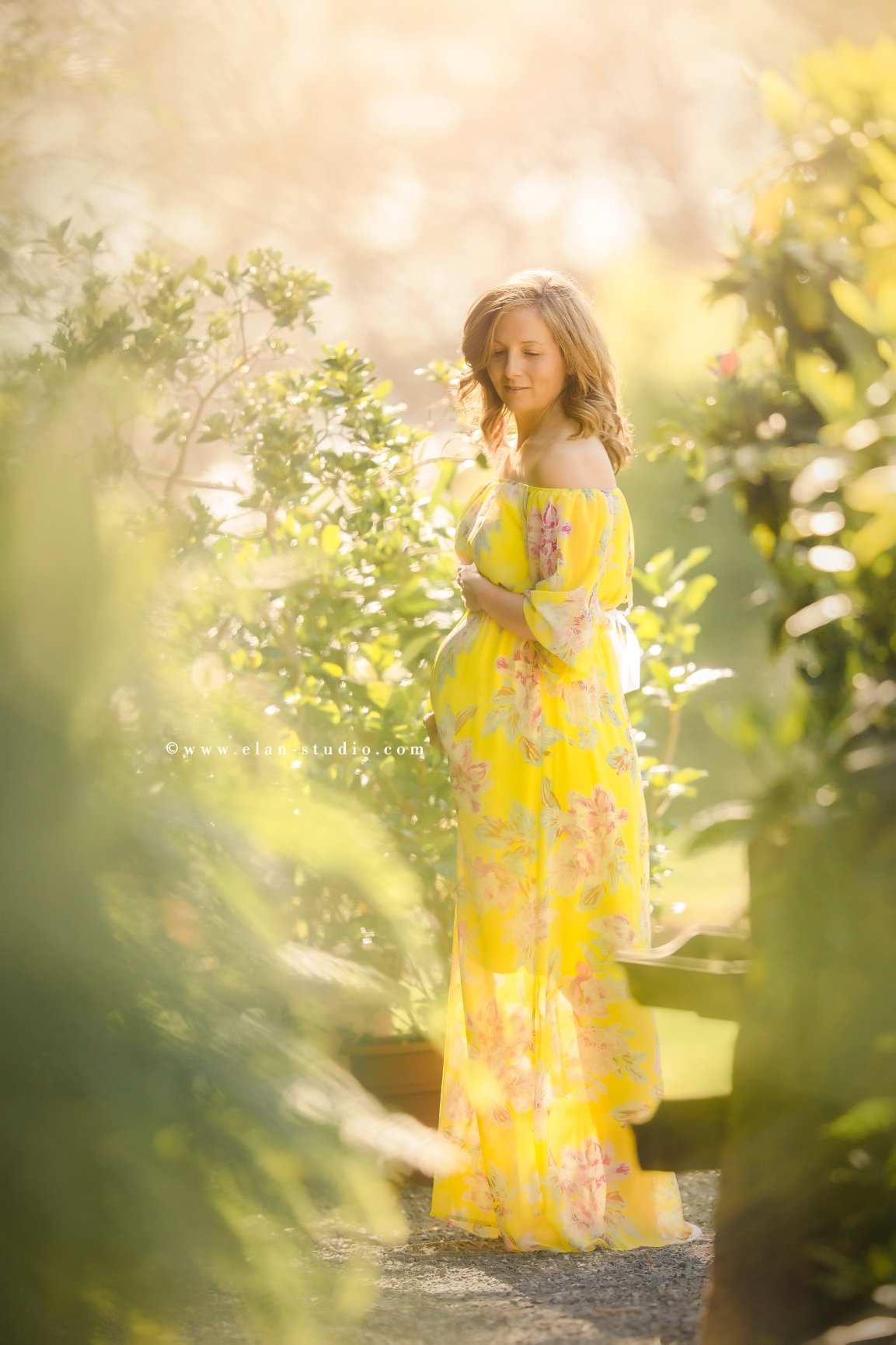 pregnant mother in yellow gown, in garden