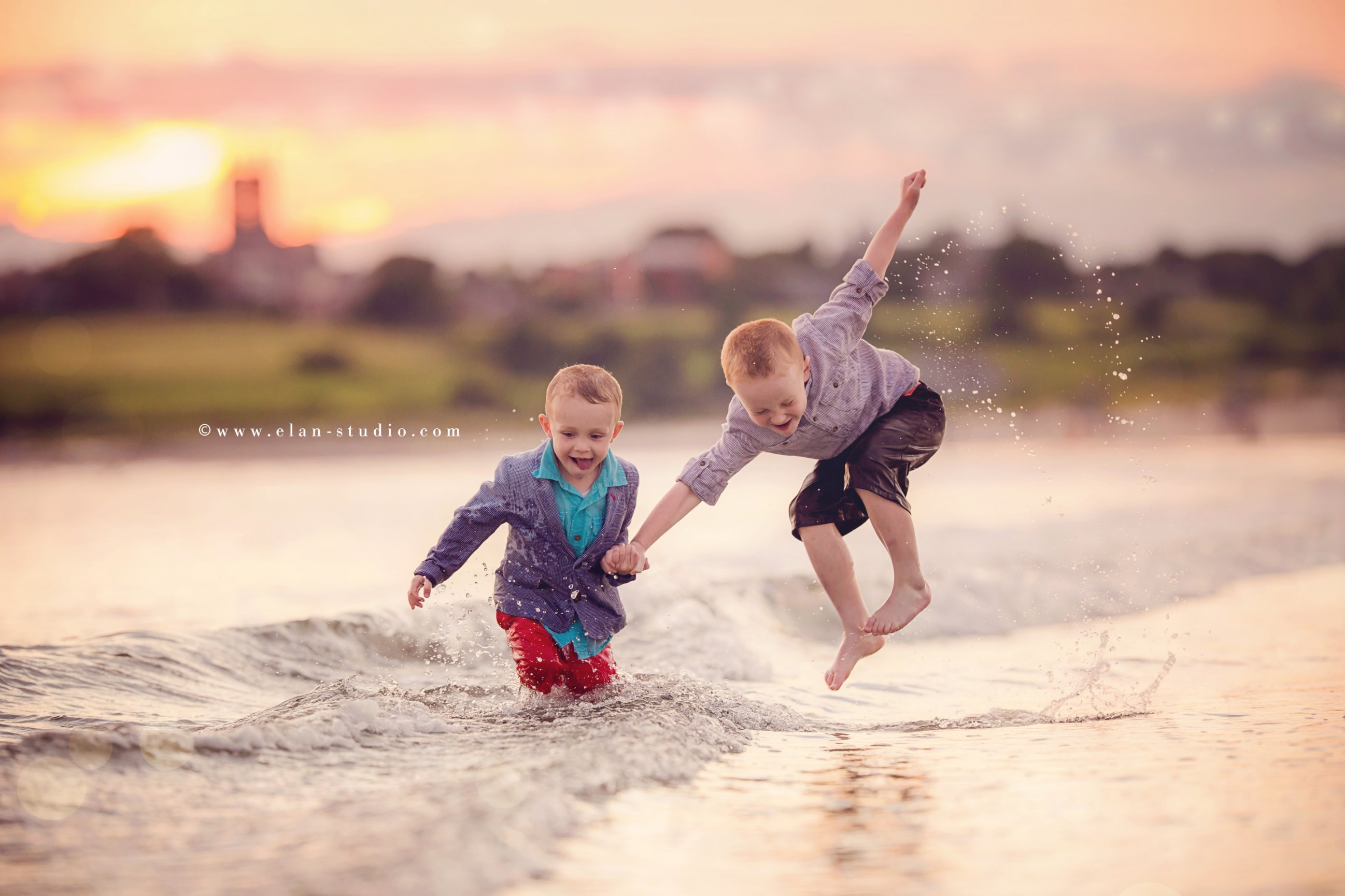 redheaded brothers playing in surf on beach
