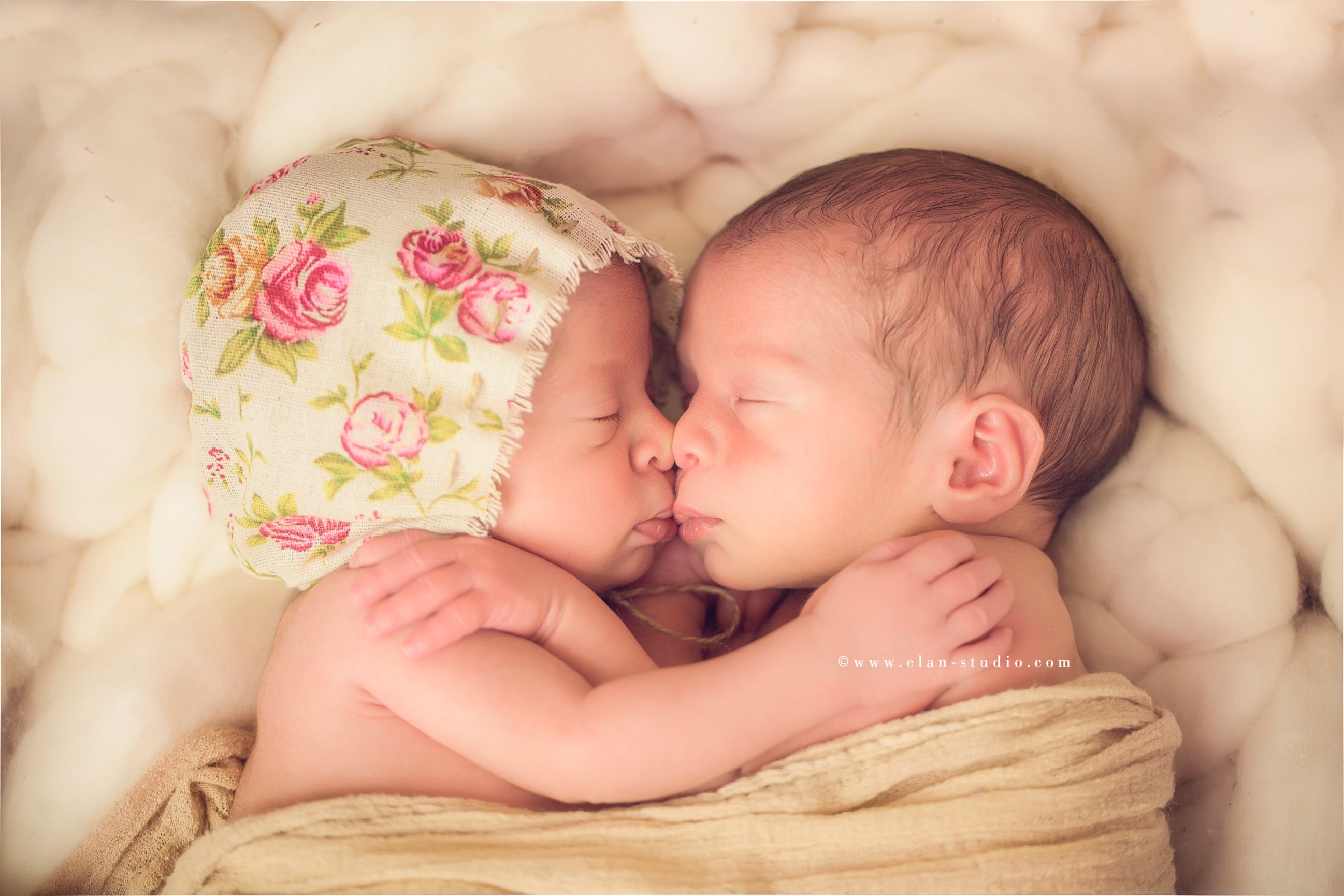 newborn twins hugging