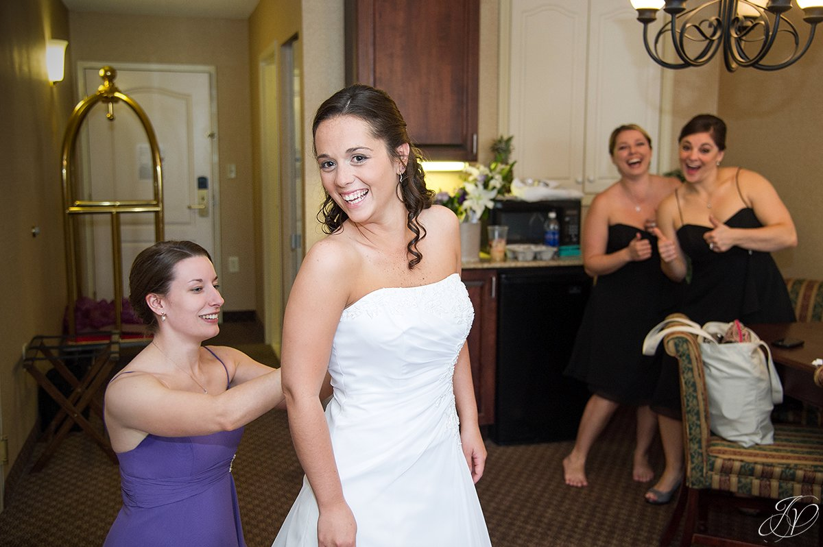 bride getting dressed with bridesmaids being silly