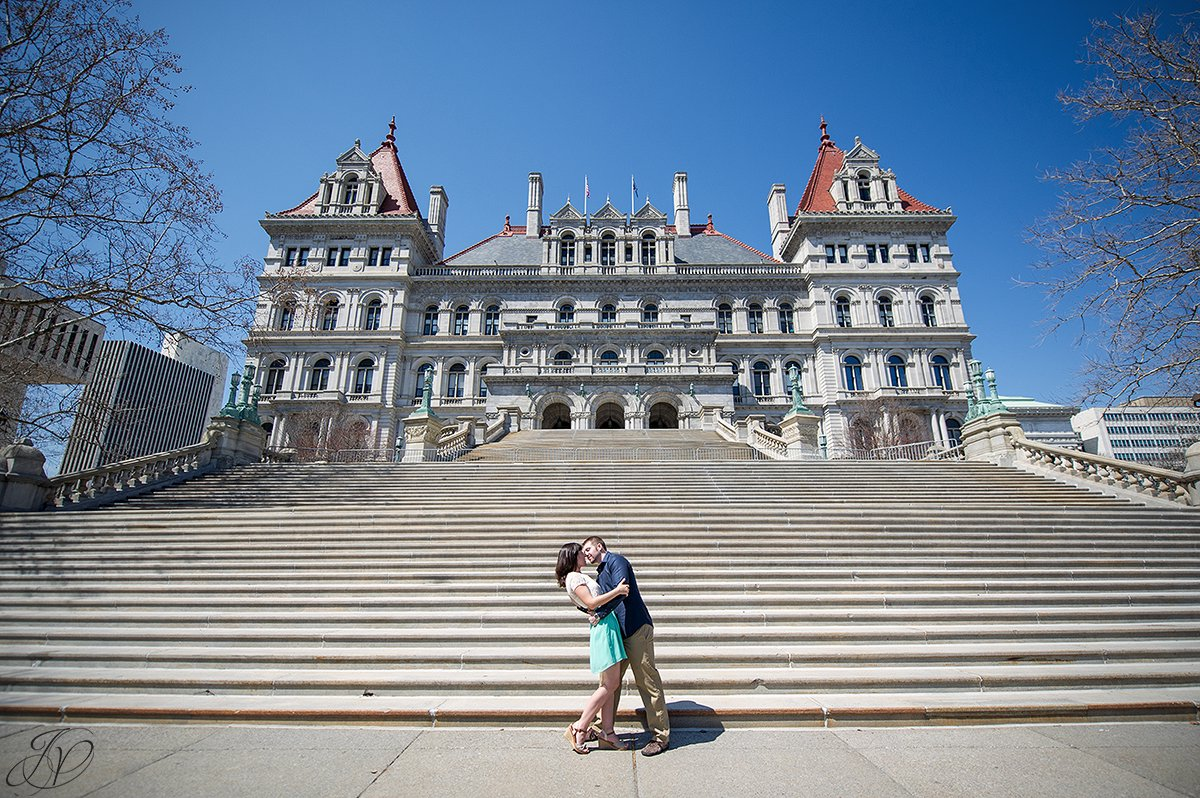 young couple kissing on stairs, couple sharing a moment on stairs of capital building, capital building albany engagement photos, albany engagement photographers, engagement session in capital building albany