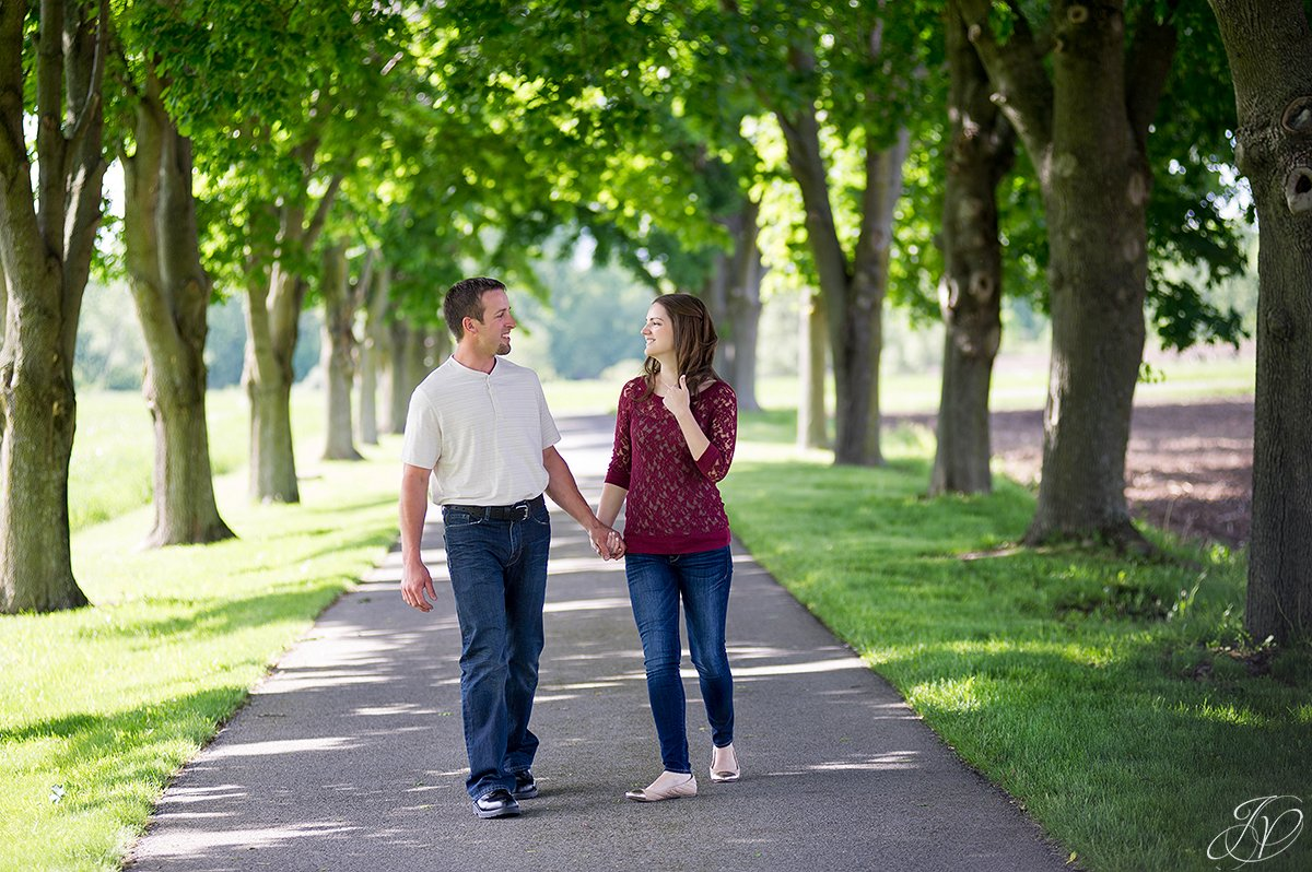 couple walking down aisle of trees