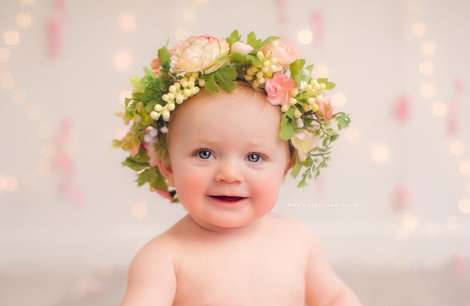 smiling baby girl with blue eyes, wearing flower crown
