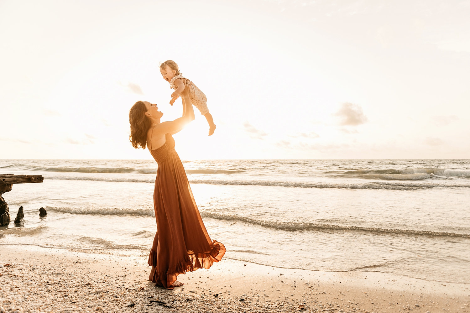 mom holding up smiling baby girl at the beach, Naples Beach, Florida, Rya Duncklee