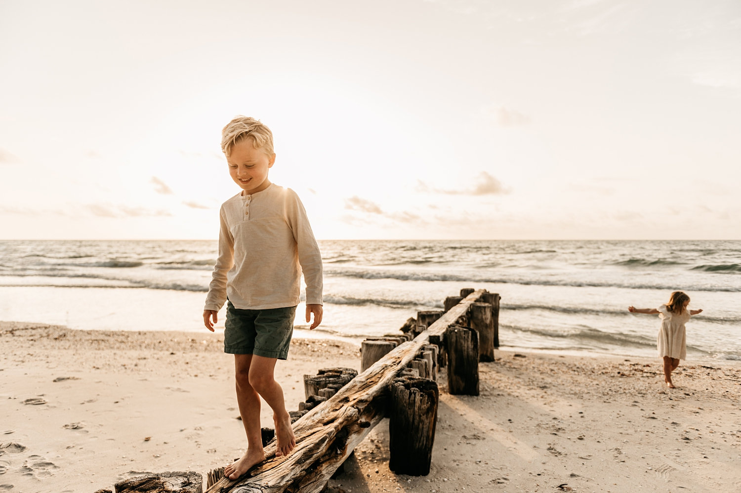 blonde boy walking on beach pilings with little sister in background, Ryaphotos