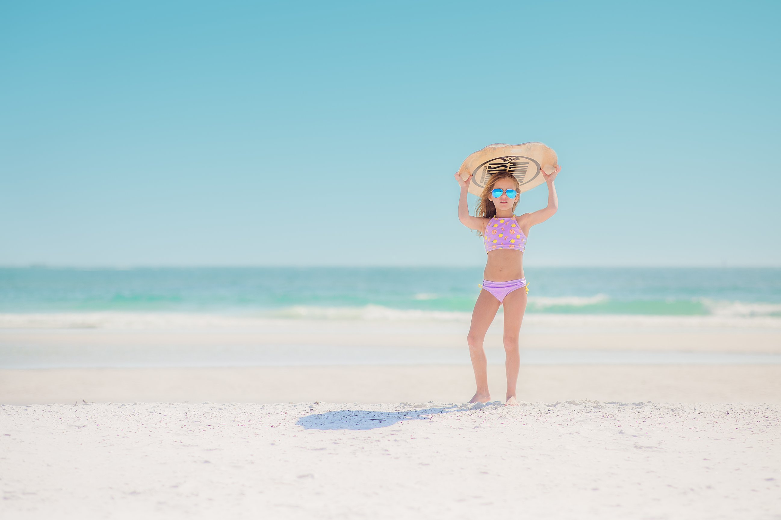 girl on beach holding surf board above head