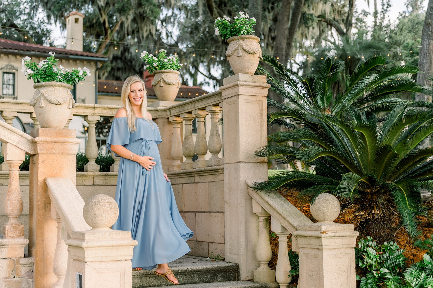 pretty pregnant woman standing on the steps in a garden of a Florida estate, there are patio lights and Spanish architectural elements