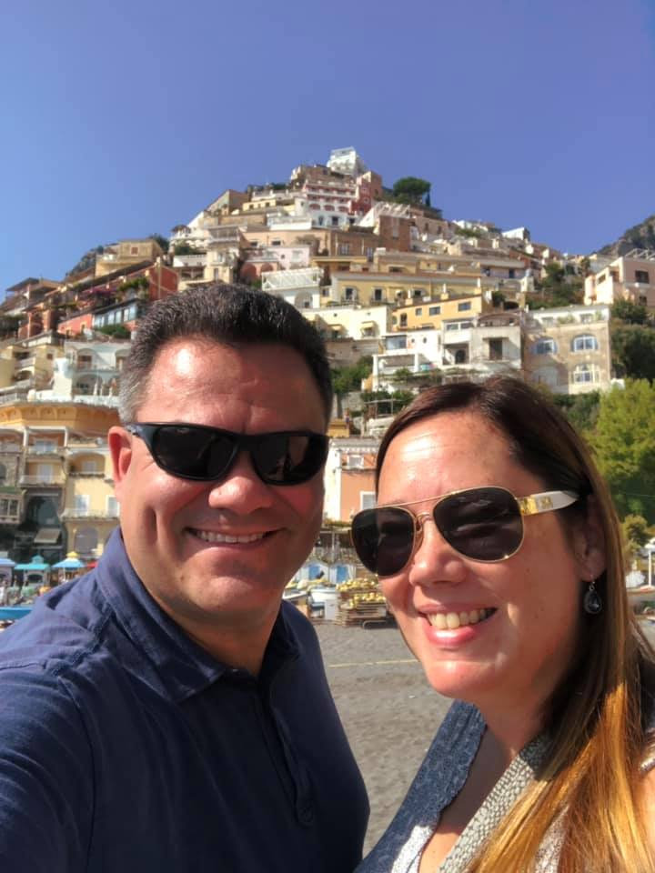 Kelly Furtado and her husband traveling overseas, Kelly and her husband are wearing sunglasses, there are buildings on a hill in the background
