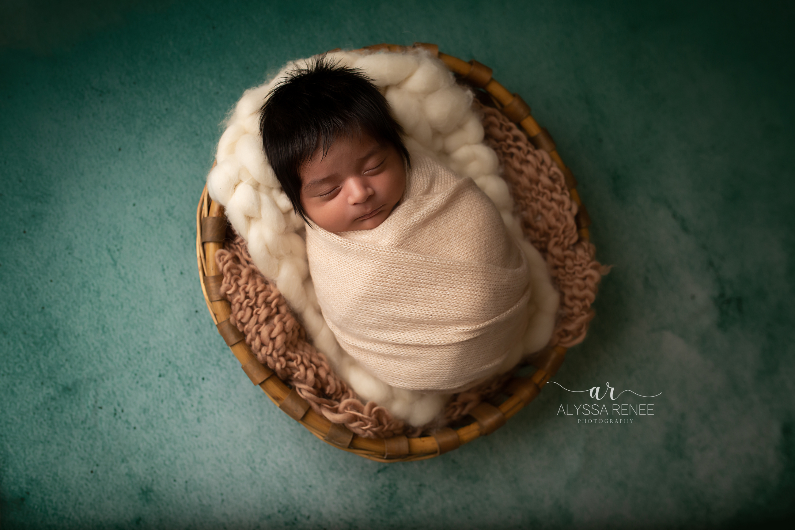 Portrait of baby swaddled in a basket on a green background with handmade prop by Alyssa Renee Photography